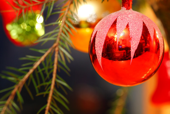 Julpynt -  Red bauble hanging in a fir tree