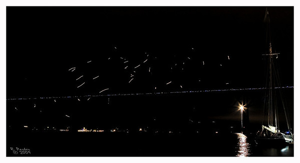 The launch of the luminaries from the Walkway Bridge in Poughkeepsie. At the bottom right you see the Sloop Clearwater and a lone Firework launched from north of the Walkway Bridge.