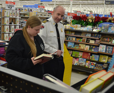 Hope Kaleto, an Edsel Ford High School sophomore, and Fire Chief Joe Murray look at books.