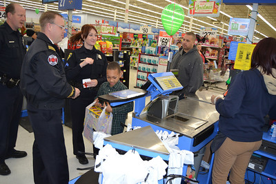 Police Cpl. Michael Maurier (left), Deputy Fire Chief Joey Thorington and police Cpl. Jane Kass wait at a cash register.