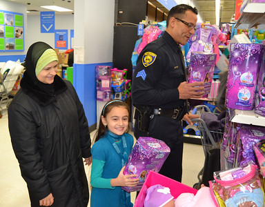 Kefaya Taha (left), Oakman Elementary School third-grader Hana Taha and police Sgt. Andreas Barnett look at dolls. (Photos by Joe Slezak)