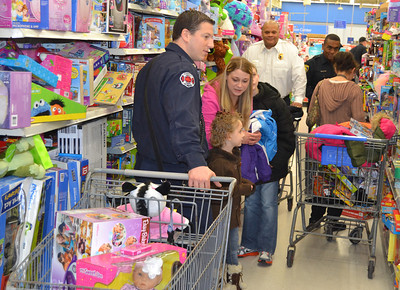 The toy section at Walmart was crowded with shoppers, including Firefighter 3 Jeff Lentz (left), fire Battalion Chief Kevin Boyer and police Cpl. Orlando Whitted. Lentz also is the new president of International Association of Fire Fighters Local 412.