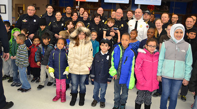 Police officers, firefighters and children pose for a group shot before the Shop With a Hero event Monday morning at Walmart.
