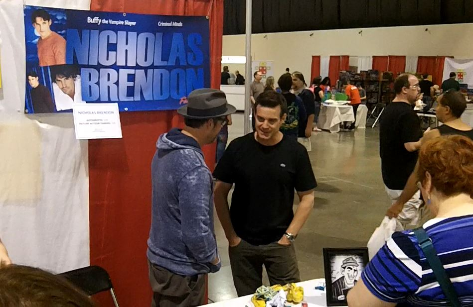 """. Actors Nicholas Brendon (left) of \""""Buffy The Vampire Slayer\"""" fame and Eddie McClintock from the hit Syfy show \""""Warehouse 13\"""" visit with each other between signings. Photo by David Komer"""