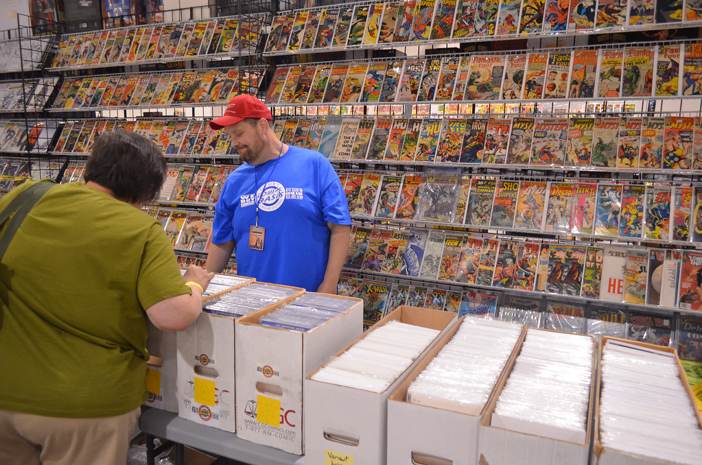 . Chatting with an early customer is John �Big Ben� Davis, owner of Big Ben�s Comix Oasis in Allen Park. Big Ben�s is the only comic shop from Downriver that participates in the Motor City Comic Con. (Photo by Dave Herndon)