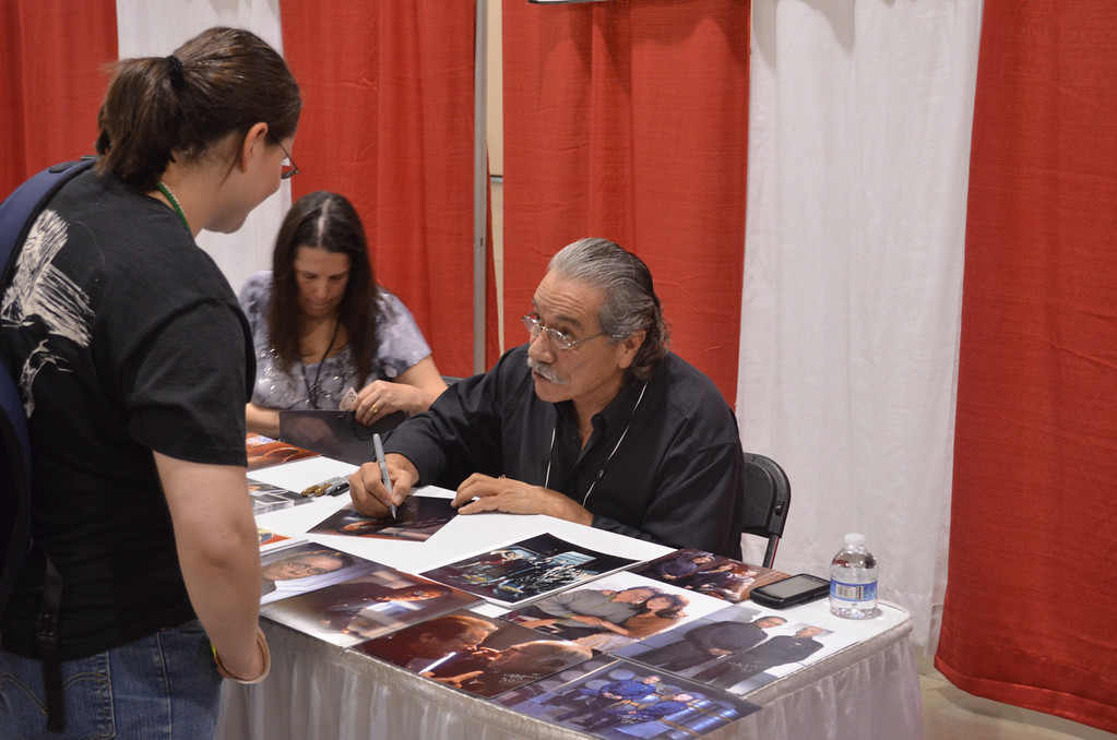 . Actor Edward James Olmos signs a photo for a fan Friday at the Motor City Comic Con in Novi. Olmos is best known for his role as Cmdr. William Adama on the rebooted �Battlestar Galactica.� The convention will be at the Suburban Collection Showplace Saturday from 10 a.m. to 6 p.m. and Sunday from 10 a.m. to 5 p.m. (Photo by Dave Herndon)