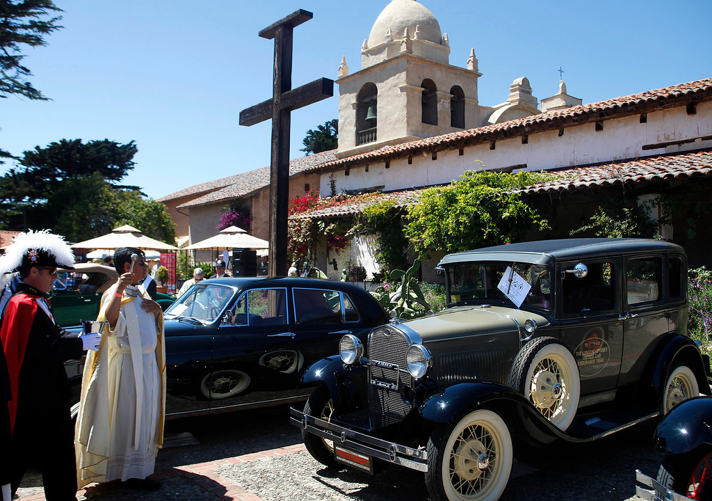 . Father Fredy Calvario blesses a 1931 Ford Model A, center, during the Blessing of the Cars at Carmel Mission in Carmel, Calif. on Wednesday August 14, 2013. At far left is Knights of Columbus member Christian Theroux. The 1931 is owned by Richard Atwell and participated in the Paris to London Road Race.  (Photo David Royal/ Monterey County Herald)