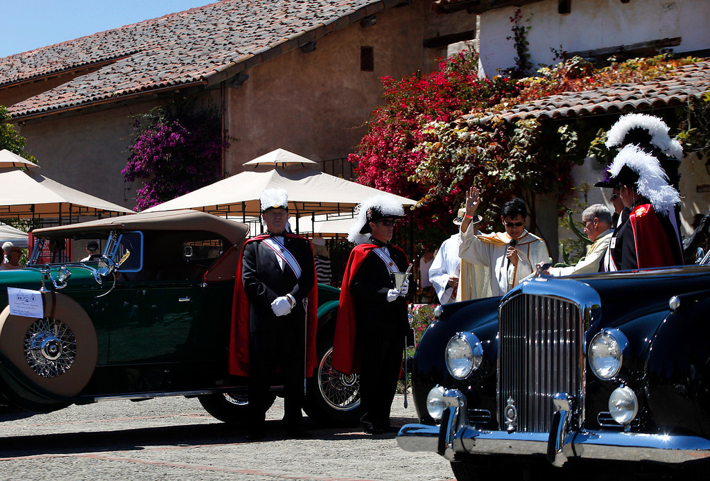 . Father Fredy Calvario is surrounded by Knights of Columbus as he says a prayer during the Blessing of the Cars at Carmel Mission in Carmel, Calif. on Wednesday August 14, 2013. At left is a 1929 Packard owned by Pat Phinny, at right is a 1951 Bentley Continental owned by Richard Atwell. The  Bentley was perviously owned by actor Cary Grant.   (Photo David Royal/ Monterey County Herald)