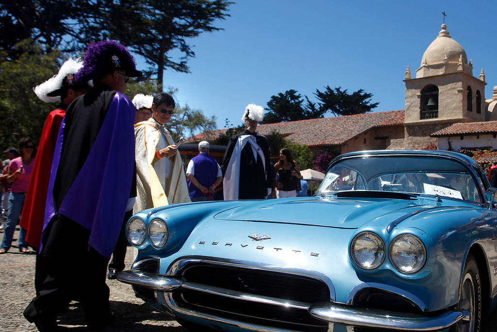. Father Fredy Calvario blesses a 1961 Chevrolet Corvette owned by david Hutchings during the Blessing of the Cars at Carmel Mission in Carmel, Calif. on Wednesday August 14, 2013.  (Photo David Royal/ Monterey County Herald)