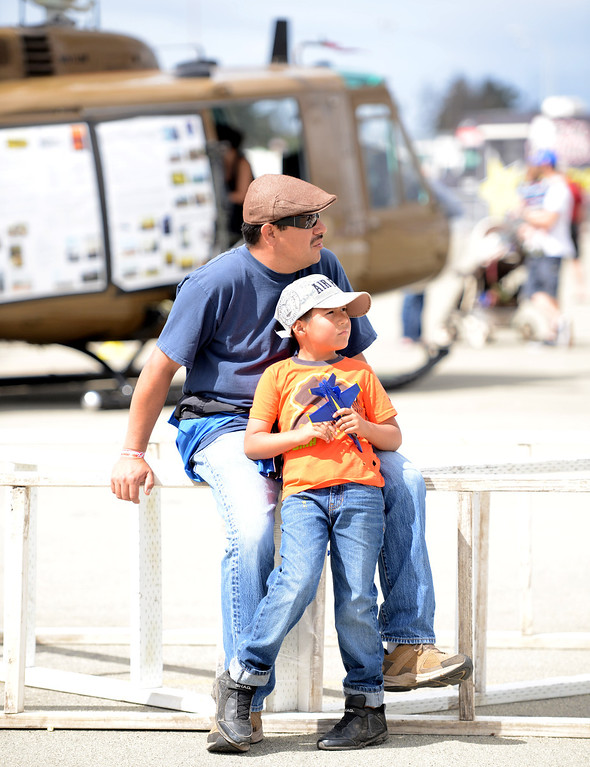 . A father and his son watch planes fly overhead during the California International Airshow Salinas at the Salinas Airport in Salinas, Calif. on Saturday September 21, 2013.  (Photo David Royal/ Monterey County Herald)