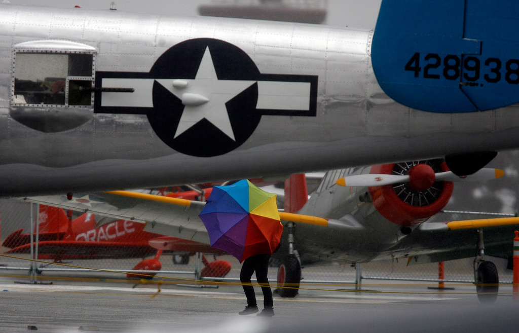 . A person with an umbrella seeks shelter behind the tail of a B-25 Mitchell as rain falls on the California International Airshow Salinas at the Salinas Airport in Salinas, Calif. on Saturday September 21, 2013.  (Photo David Royal/ Monterey County Herald)