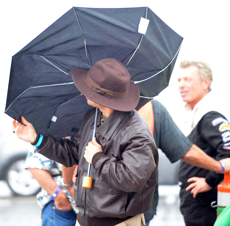 . Richard Berghoff tries to salvage his umbrella as stunt pilot Shawn D. Tucker, right, waits for the rain to pass so he can fly during the California International Airshow Salinas at the Salinas Airport in Salinas, Calif. on Saturday September 21, 2013.  (Photo David Royal/ Monterey County Herald)