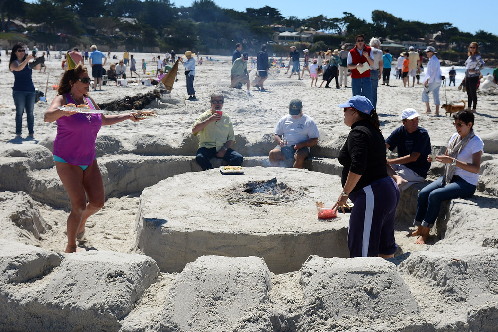. A group of friends from Carmel eat lunch in a seating area castle they dug from the sand during the Sand Castle Contest on Carmel Beach in Carmel, Calif. on Sunday September 15, 2013. (Photo David Royal/ Monterey County Herald)