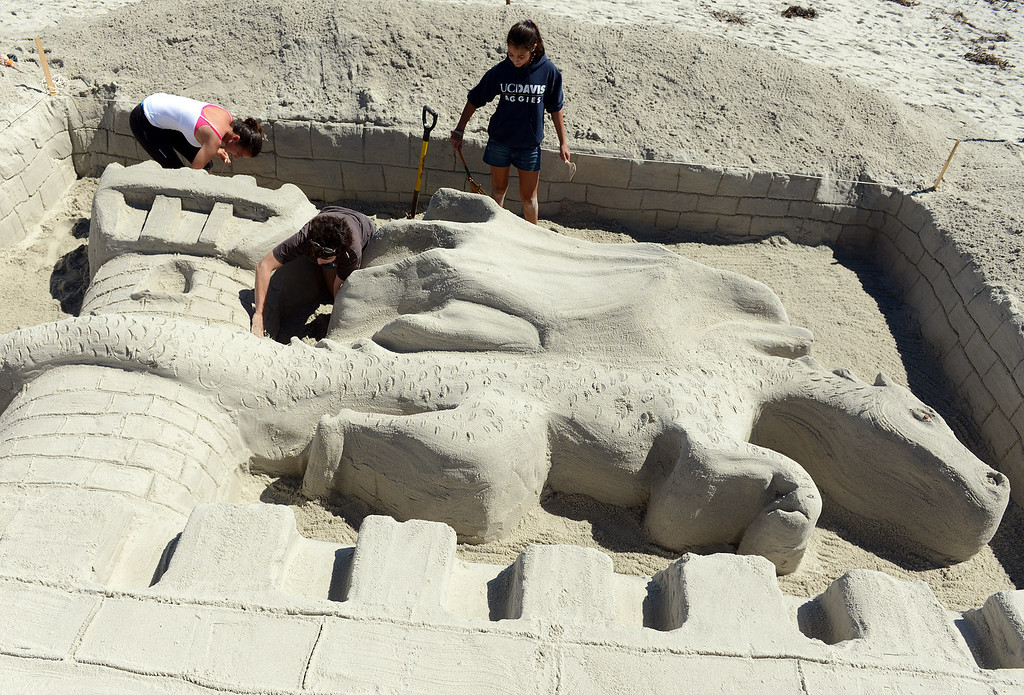 . Pilar Batillo, center, of Palo Alto gets help her niece Melissa Crane, right, and friend Andrea Clerici putting the finishing touches on their dragon castle during the Sand Castle Contest on Carmel Beach in Carmel, Calif. on Sunday September 15, 2013. This years theme was Once Upon a Castle. (Photo David Royal/ Monterey County Herald)