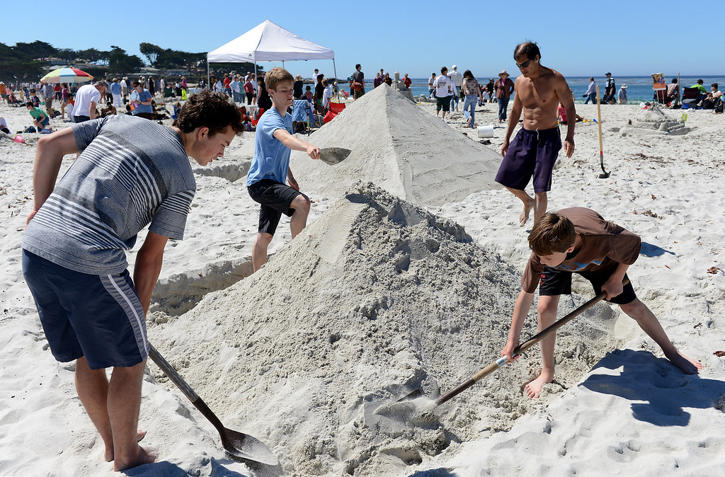 . Eugene Loh, clockwise from center right, of Pacific Grove works on a sand castle version of the Great Pyramids of Giza with sons Henry, 13, Jacob, 17 and friend Eric O\'Hagan during the Sand Castle Contest on Carmel Beach in Carmel, Calif. on Sunday September 15, 2013. (Photo David Royal/ Monterey County Herald)