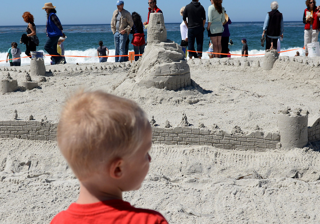 . A boy looks over the castle built by Carmel River School students during the Sand Castle Contest on Carmel Beach in Carmel, Calif. on Sunday September 15, 2013. (Photo David Royal/ Monterey County Herald)