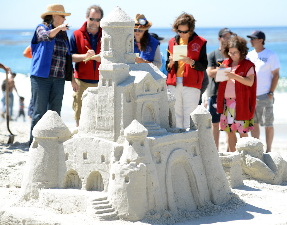 . Sand Castle Contest judges take a close look at the Storybook Dreams which had a castle rising out of a book that a child was reading at Carmel Beach in Carmel, Calif. on Sunday September 15, 2013. The castle, built by the Mehringer Family of Monterey, won the Golden Shovel Award. (Photo David Royal/ Monterey County Herald)