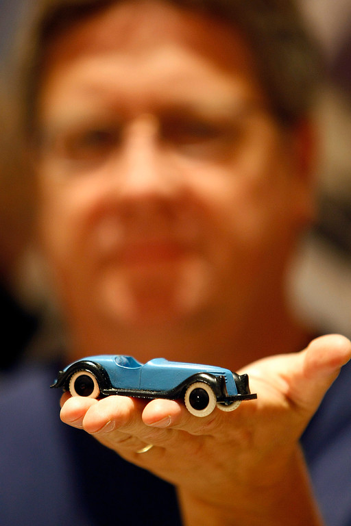 . Sam Halsted holds a toy sports car cicra 1950s made in Italy, one of his rarer items on sale at the Automobilia Monterey International Expo at the Embassy Suites in Seaside on August 13, 2013.  (Vern Fisher/Monterey County Herald)