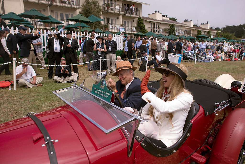. Rob and Melani Walton wave to spectators as they cue up in front of the Concours d\'Elegance stage Sunday, August 18th, 2013 in in their 1931 Alfa Romeo 8C 2300 Le Mans Spider. (Matthew Hintz/Monterey County Herald)