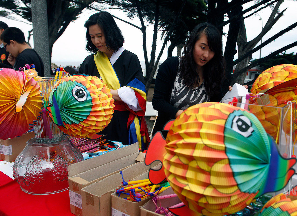 . Sonhee Cho, right and her mother Meesun Cho prepares a lighted lantern for sale while volunteering during Feast of Lanterns festivities at Lovers Point Pacific Grove, Calif. on Saturday July 26, 2013.  (Photo David Royal/ Monterey County Herald)