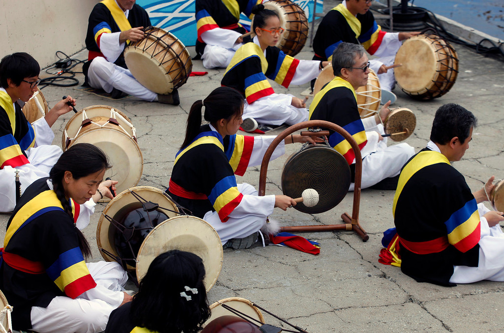 . Soondeuk Lowney, lower left, performs Samulnori traditional Korean drumming with a group from the Korean School of Monterey during Feast of Lanterns festivities at Lovers Point Pacific Grove, Calif. on Saturday July 26, 2013.  (Photo David Royal/ Monterey County Herald)
