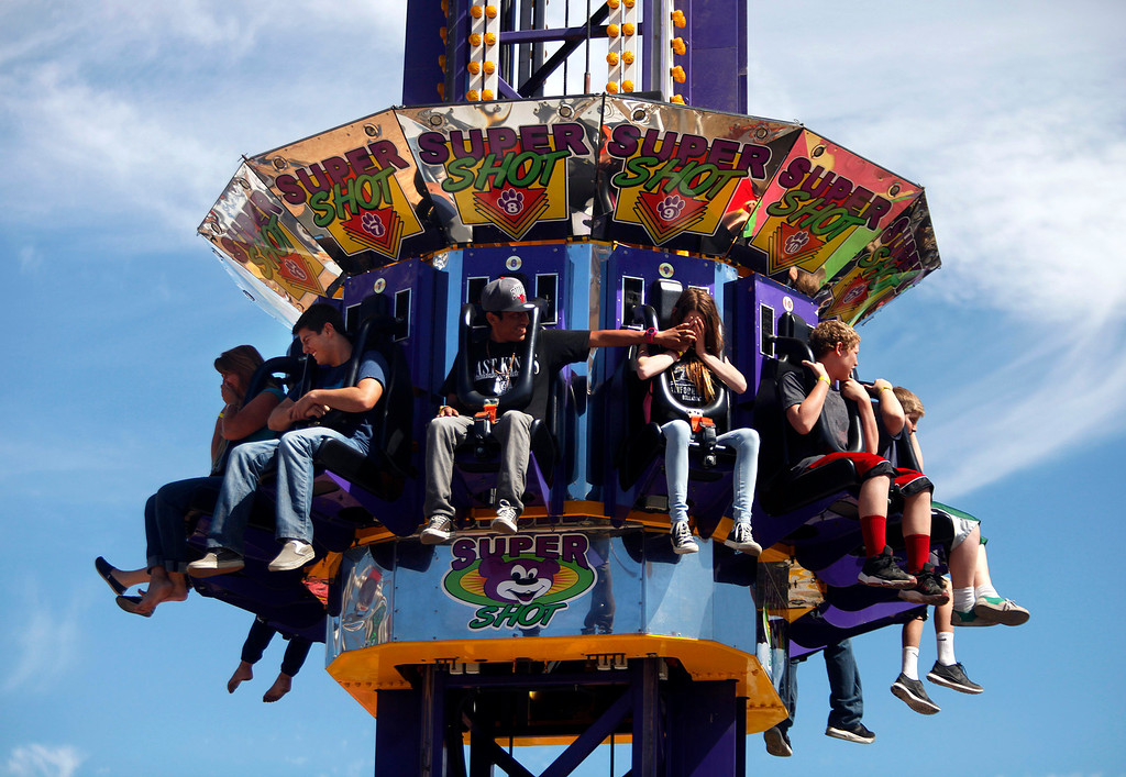 . Lupe Sebastian, 15, center left, of Seaside helps his friend Megan Goodfield, 14, of Pacific Grove cover her eyes as they are elevated into the sky on the Super Shot ride at the Monterey County Fair in Monterey, Calif. on Sunday September 1, 2013. The ride lifts riders several stories into the sky before dropping them straight down. (Photo David Royal/ Monterey County Herald)