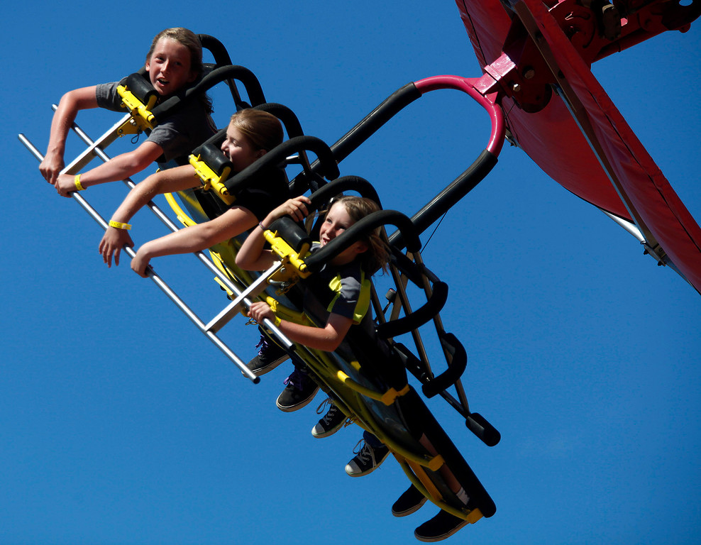 . Jake Haney, 12, left, his brother Gavin, 9, right, and their cousin Gabi DaSilva, 12, all of Pacific Grove ride the Cliff Hanger ride at the Monterey County Fair in Monterey, Calif. on Sunday September 1, 2013.  (Photo David Royal/ Monterey County Herald)