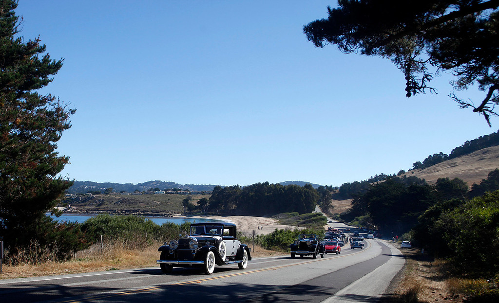 . A 1930 Cadillac 452 Fleetwood Coupe owned by Rudy Langer leads a line of classic cars past Monastery Beach on their way south toward Big Sur on Highway 1 during Pebble Beach Tour d�Elegance in Carmel, Calif. on Thursday August 15, 2013. The Route starts in Pebble Beach, passes through Laguna Seca Raceway, Carmel Valley and Big Sur before returning to the Monterey Peninsula.  (Photo David Royal/ Monterey County Herald)