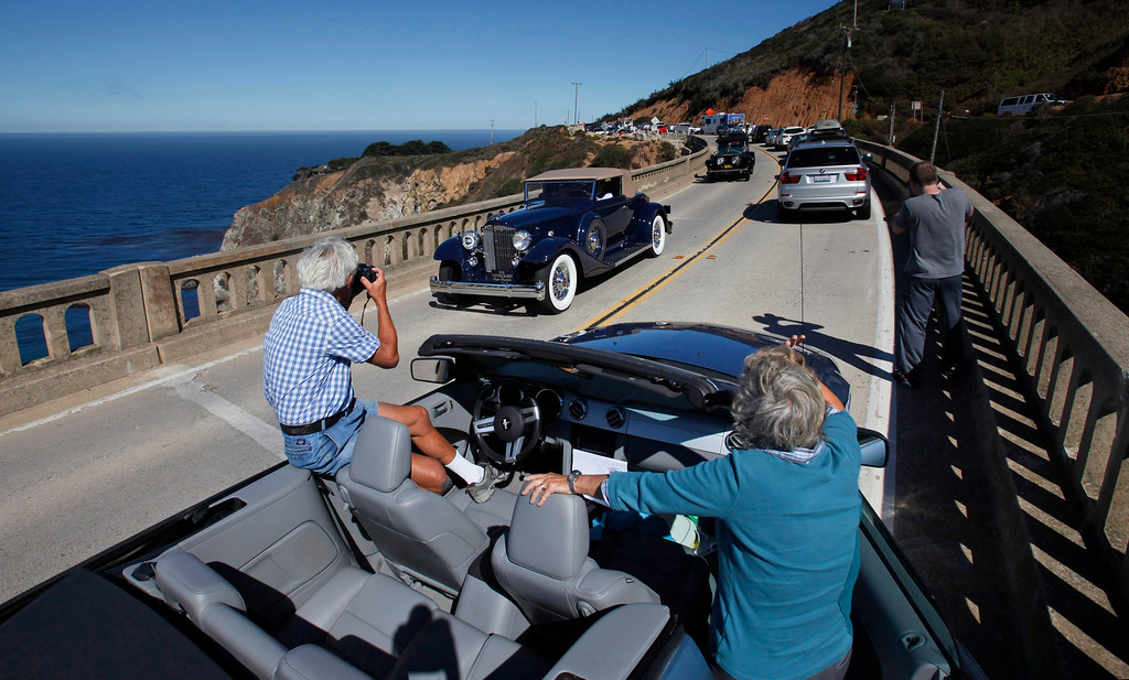 . Mike and Myrna Sonstein from Oceanside stop to photograph passing classic cars on  Highway 1 over the Bixby Creek Bridge during the Tour d\'Elegance on August 15, 2013.  (Vern Fisher/Monterey County Herald)