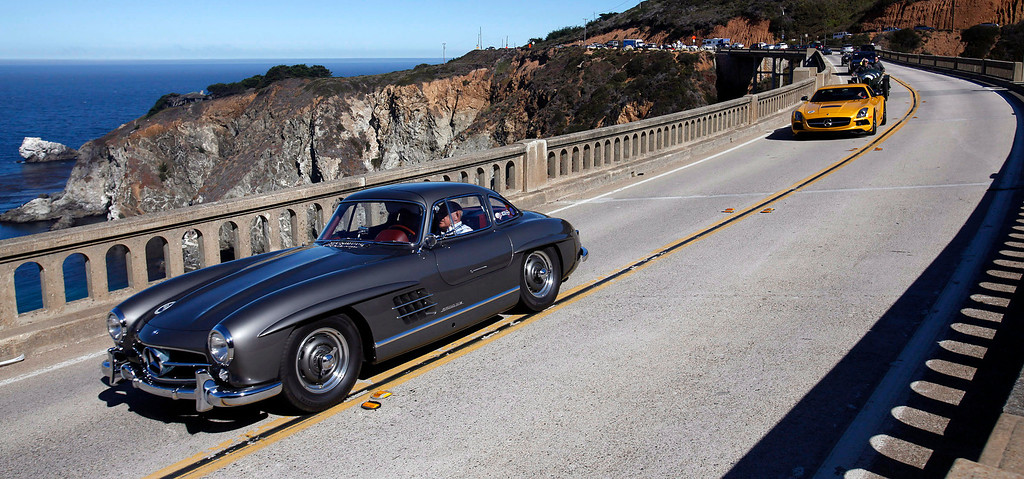 . Sir Stirling Moss leads a group of classic cars south on Highway 1 over the Bixby Creek Bridge during the Tour d\'Elegance on August 15, 2013.  (Vern Fisher/Monterey County Herald)