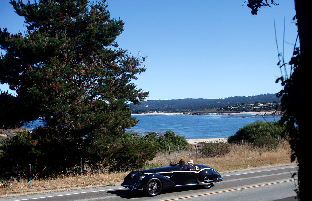 . A classic car rolls past Monastery Beach on it\'s way south toward Big Sur on Highway 1 during Pebble Beach Tour d�Elegance in Carmel, Calif. on Thursday August 15, 2013. The Route starts in Pebble Beach, passes through Laguna Seca Raceway, Carmel Valley and Big Sur before returning to the Monterey Peninsula.  (Photo David Royal/ Monterey County Herald)