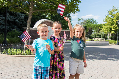 Noah, Ava and Ally Pouliot received flags from Bank of America volunteers. Photo by Debbie Malyn for the Press & Guide.