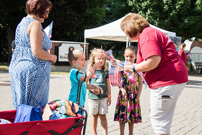 Noah, Ava and Ally Pouliot receive flags from Bank of America volunteers. Photo by Debbie Malyn for the Press & Guide.
