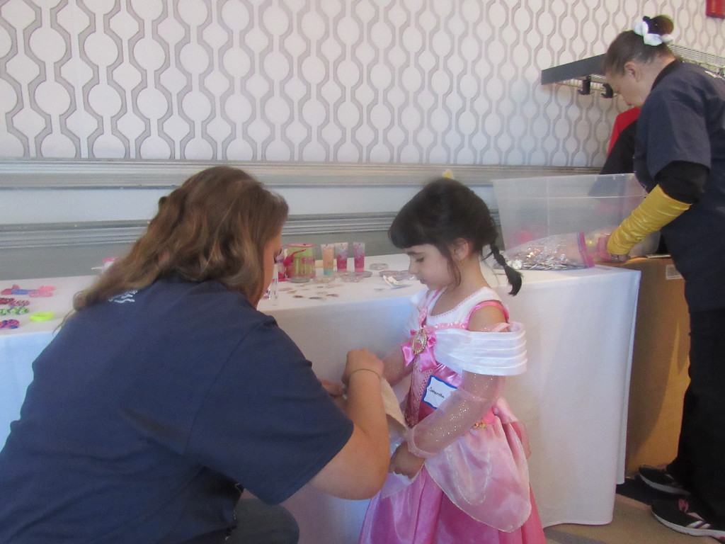 . A volunteer puts on a temporary tattoo for a guest at the 8th Annual Princess and Superhero Party Sunday, May 7.  Photo by Micah Walker