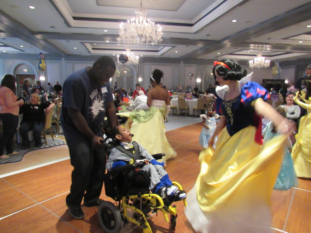 . A wheelchair-bound child gets a chance to dance with Snow White at the Princess and Superhero Party Sunday, May 7.