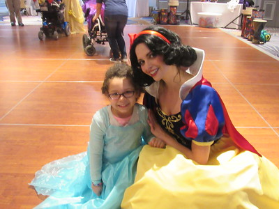 Kristie Fox, dressed up as Snow White, poses with a guest at the 8th annual Princess and Superhero Party.