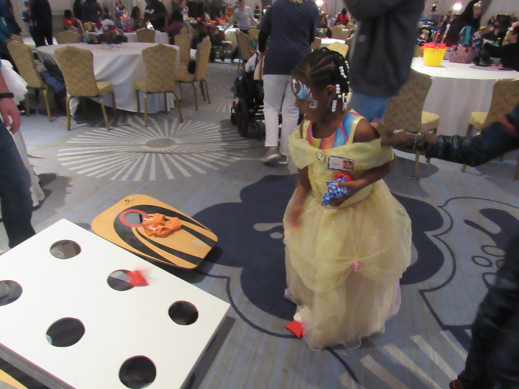 . A child dressed up as Belle from Beauty and the Beast plays a game of Bean Bag Toss.