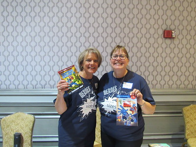 Volunteers Marianne Tucker and Barb Sturtz passed out superhero and princess books at the party.