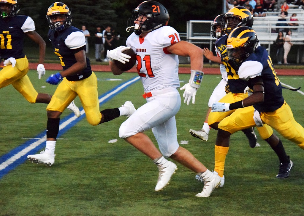 . Dearborn High\'s Jake Tafelski (21) races past a group of Wayne Memorial defenders on Friday night. Tafelski and the visiting Pioneers rolled to a 52-6 victory. Alex Muller - For Digital First Media