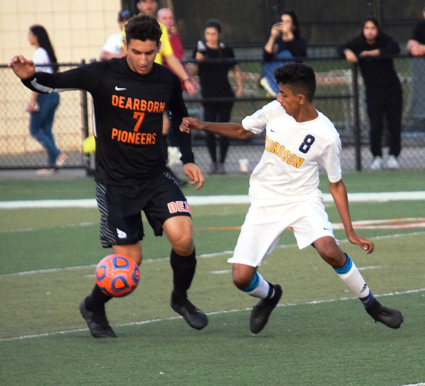. Dearborn High\'s Kamal Kabbani (7) is defended by Fordson\'s Murad Othman during Tuesday\'s battle between the two in-city rivals. Kabbani and the host Pioneers ultimately came away with a 2-0 victory and moved into a first-place tie with the Tractors in the KLAA East. Alex Muller - For Digital First Media
