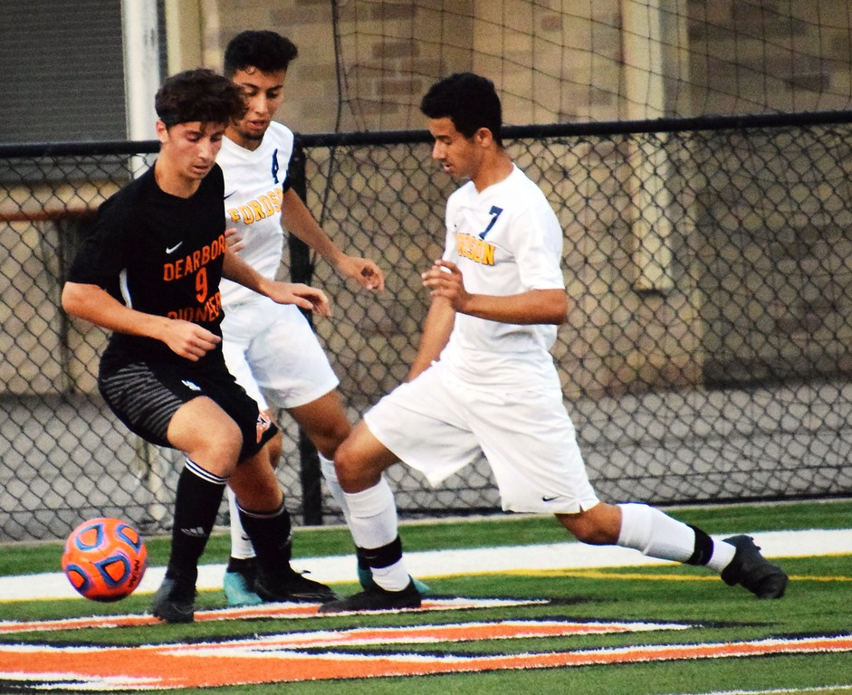 . Fordson\'s Ahmad Hamad (7) and Hassan Jaber (4) battle with Adam Khreiss of host Dearborn High during Tuesday\'s big KLAA East meeting. The Tractors went on to fall by a score of 2-0 and slipped into a first-place tie with the Pioneers. Alex Muller - For Digital First Media