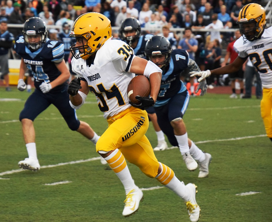 . Fordson\'s Abe Jaafar carries the ball on Friday night at Livonia Stevenson. He helped guide the Tractors to a 45-14 win over the Spartans in the KLAA East battle. Alex Muller - For Digital First Media