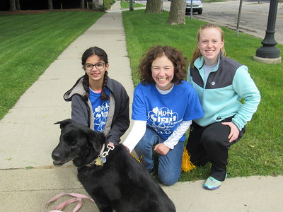 Volunteers for the Mutt Strut pose with Tucker, a Australian Shepherd Labrador.
