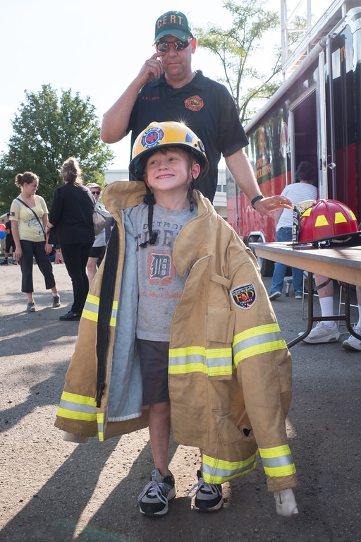 . Griffin Sullivan, age 5 from Dearborn, tries on some Fire Department gear. Photo by Debbie Malyn for the Press & Guide.