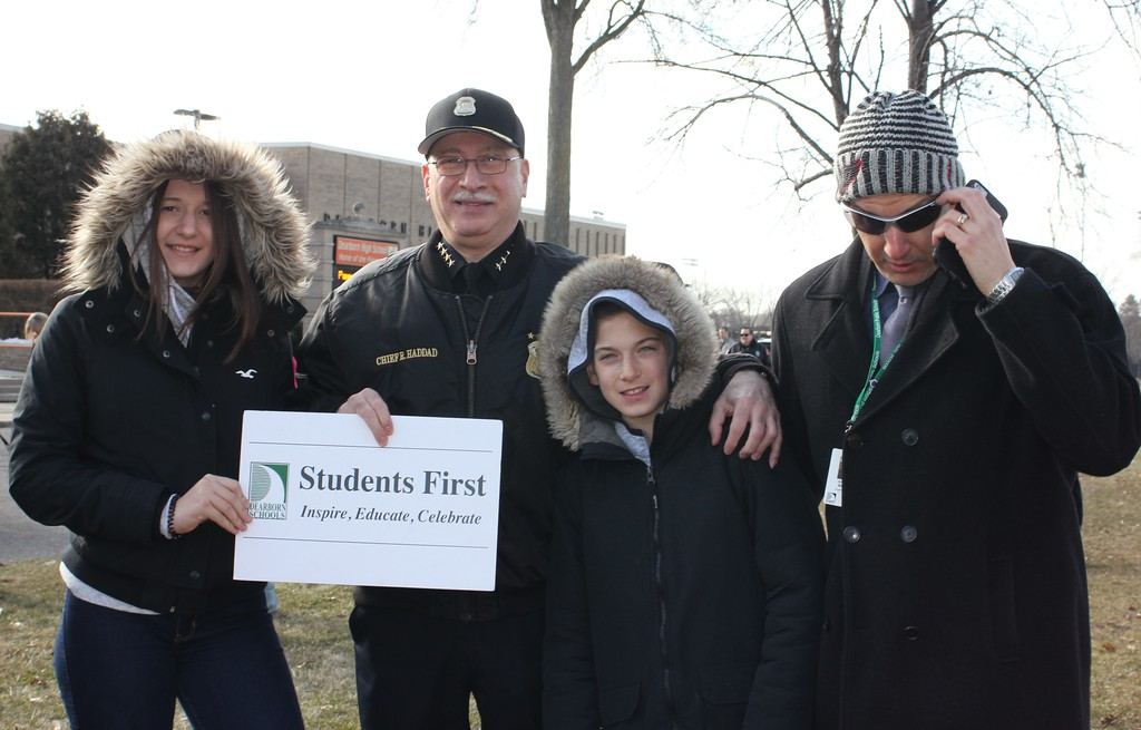 . Dearborn Police Chief Ronald Haddad (second from left) stands with Ashley and Justin Maleyko, and their father, Dearborn Public Schools Supt. Glenn Maleyko, at Wednesday\'s walkout at Dearborn High School. Photo by Sue Suchyta -- For The Press & Guide
