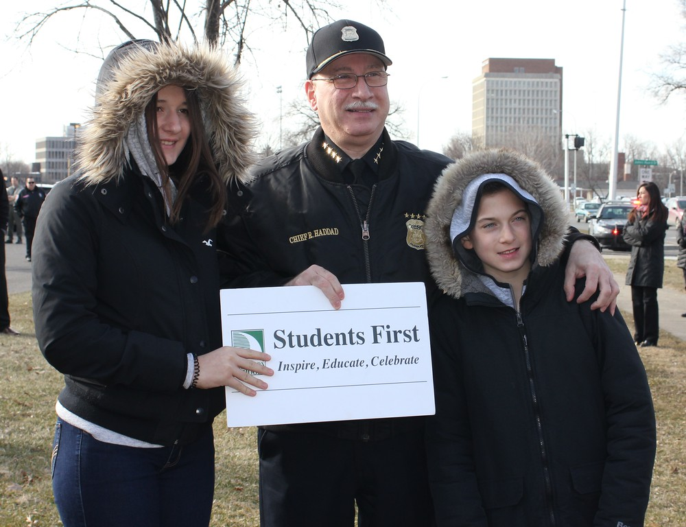 . Dearborn Police Chief Ronald Haddad stands with Ashley and Justin Maleyko, the children\' of Dearborn Public Schools Supt. Glenn Maleyko, at Wednesday\'s walkout at Dearborn High School. Photo by Sue Suchyta -- For The Press & Guide