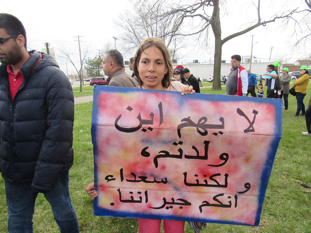 """. Carla Valpeoz of Dearborn attended the Neighbors Building Bridges March April 2. Her sign reads, \""""No matter where we come from, we must all stick together as neighbors.\"""""""