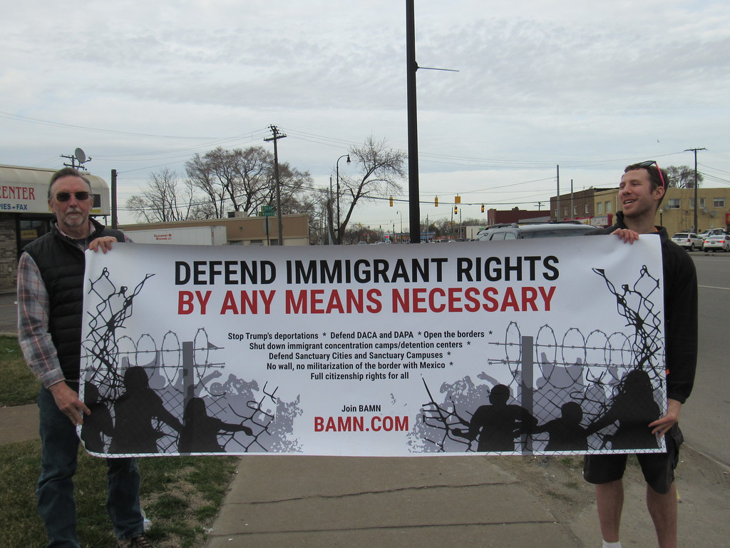 . From left to right: Michael Mulholland and Tyler Wood from the organization By Any Means Necessary (BAMN) show their support for immigration and refugee rights at the march.