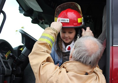 Aubrey Locklear, 11, of Taylor is fitted with a fire hat by retired Redford Township Fire Chief Les Wedge Oct. 29 while visiting the Dearborn Fire Safety House Pumpkin Patch.