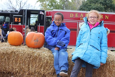 Dearborn residents William Turner (left), 8, and Celise Helfer, 10, wait with their pumpkins Oct. 29 while their friends from Stephens United Methodist Church, 5000 Pelham, Dearborn Heights, make their selections at the Dearborn Fire Safety House Pumpkin Patch.